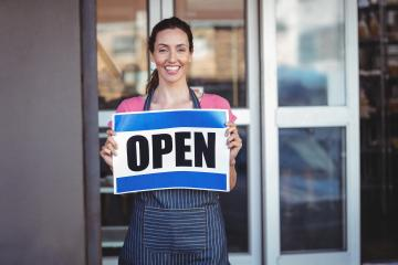 Woman holding an open sign outside of business